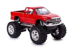 Voiture rouge de jouet grand en métal tous terrains avec des roues de monstre d'isolement sur le fond blanc Image stock