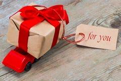 Voiture rouge de jouet livrant le boîte-cadeau pour le jour du ` s de Valentine avec des WI d'étiquette Image stock