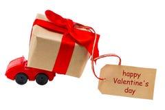 Voiture rouge de jouet livrant le boîte-cadeau pour le jour du ` s de Valentine avec l'esprit d'étiquette Photo stock