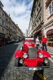 Voiture rouge de vintage devant le château de Prague Images stock