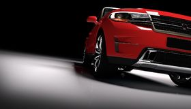 Voiture rouge moderne de SUV dans un projecteur sur un noir Photographie stock libre de droits
