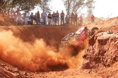 Voiture rouge montant la pirogue raide, donnant un coup de pied le sable et la poussière Images stock