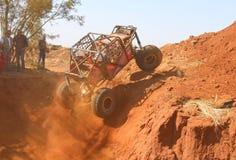 Voiture rouge ramping hors de la pirogue raide, trois roues suspendues Images libres de droits