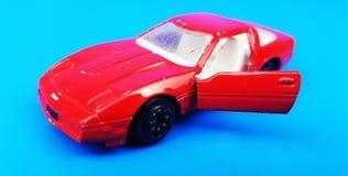 Voiture rouge sur le fond bleu avec la porte ouverte Modèle de voiture de jouet Photographie stock
