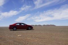 Voiture rouge sur Stuart Highway dans l'Australie d'intérieur Photos stock