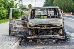 Voiture rouillée brûlée sur la route Photographie stock libre de droits