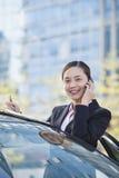 Voiture se tenante prêt de femme d'affaires utilisant le téléphone, regardant l'appareil-photo Photographie stock libre de droits