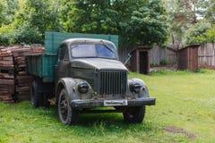 Voiture soviétique antique dans le pré vert et le vieil outd en bois abandonné Images stock