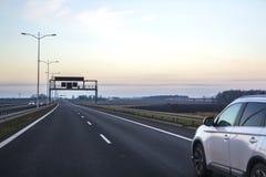 Voiture sur la route avec les panneaux routiers directionnels vides Image libre de droits