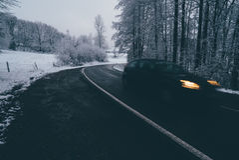 Voiture sur la route d'hiver par la forêt Images stock