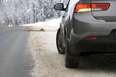 Voiture sur le chemin forestier en hiver Photos stock