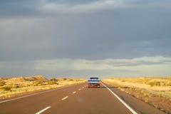 Voiture sur une longue route à l'horizon de ciel Photographie stock libre de droits