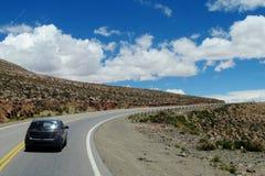 Voiture sur une longue route à l'horizon de ciel Images libres de droits