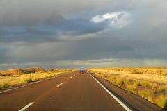 Voiture sur une longue route à l'horizon de ciel Images stock