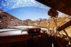 Voiture SUV sur la vue de fenêtre de fond de montagnes Photo stock