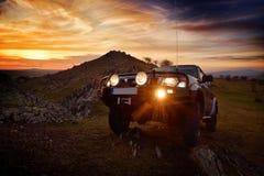 Voiture tous terrains sur la route de montagne au coucher du soleil Photographie stock libre de droits