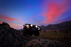 Voiture tous terrains sur la route de montagne au coucher du soleil Photos stock