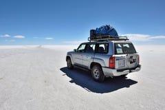 Voiture tous terrains sur la surface du lac Salar de Uyuni Images libres de droits