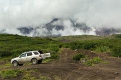 Voiture tous terrains sur un fond de volcan d'Avacha ou Avachinskaya Sopka sur la péninsule de Kamchatka Images stock