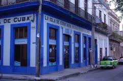 Voiture verte classique devant un bâtiment bleu vif Photos libres de droits