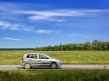 Voiture voyageant le long d'une route de campagne Photographie stock