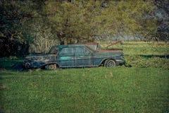 Voitures anciennes abandonnées par épave dans le pré ouvert Image libre de droits