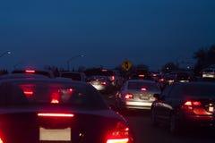 Voitures arrêtées dans des lumières de queue de soirée du trafic Photographie stock