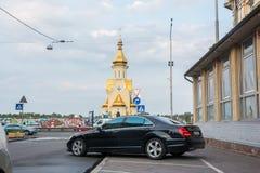 Voitures chères et une église dans Podil, Ukraine, Kyiv éditorial 08 03 2017 Photo libre de droits