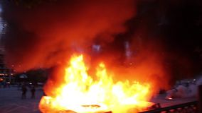 2 voitures de cannette de fil brûlent tandis que les dirigeants d'émeute jettent le gaz lacrymogène banque de vidéos