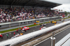 Voitures de course sur la grille commençante Le foyer sur la balustrade avec la pluie chute Photographie stock