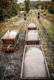 Voitures de fret avec la pierre écrasée sur le chemin de fer Images stock