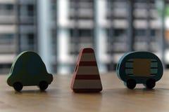 Voitures en bois de jouet avec le pylône du trafic sur la table Photo stock