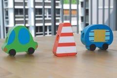 Voitures en bois de jouet avec le pylône du trafic sur la table Image libre de droits
