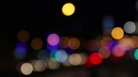 Voitures et bâtiments mobiles avec l'illumination à la ville de nuit hors focale banque de vidéos