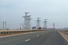 Voitures et camions conduisant sur la route à l'arrière-plan des lignes de transmission dans la région de Volgograd Photo stock