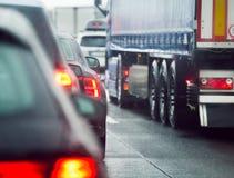 Voitures et camions d'embouteillage conduisant sur la route de route photographie stock