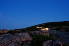 Voitures laissant le dessus de la montagne de Cadillac après coucher du soleil avec le ligh Images libres de droits
