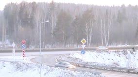 Voitures mobiles sur la route dans la forêt à l'hiver clips vidéos