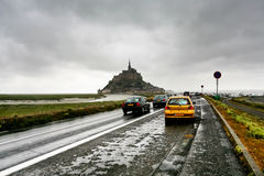 Voitures sur la route et le Mont Saint-Michel humides, France Photos stock