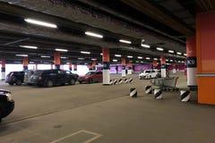 Voitures sur un grand stationnement souterrain dans le méga de centre commercial photos stock