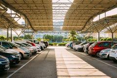 Voitures sur un parking dans le jour d'été ensoleillé dedans Images libres de droits