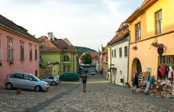 Voitures, touristes et maisons sur des rues de la ville médiévale de Sighisoara, Roumanie Bâtiments et cafés antiques de rue photographie stock libre de droits