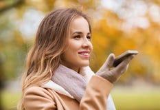 Voix d'enregistrement de femme sur le smartphone en parc d'automne images libres de droits