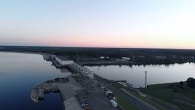 Vol aérien au-dessus de la centrale hydroélectrique sur la rivière de dvina occidentale à Riga dans le coucher du soleil égalisan banque de vidéos