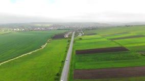 Vol aérien au-dessus de la route avec des voitures séparant les champs verts Jour brumeux et l'itinéraire qui relie la ville banque de vidéos
