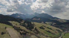 Vol aérien au-dessus de paysage de ressort avec des nuages se déplaçant au-dessus du laps de temps de montagnes banque de vidéos