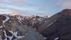 Vol aérien au-dessus des montagnes volcaniques neigeuses et delta de rivière en égalisant l'Islande banque de vidéos