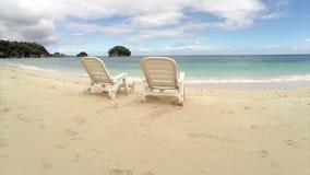 Vol aérien : chaise deux vide sur une plage par l'océan banque de vidéos