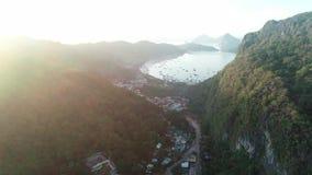 Vol aérien de bourdon entre les montagnes couvertes de forêt tropicale le temps de lever de soleil Baie tropicale de paradis avec clips vidéos