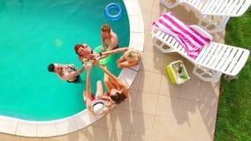 Vol aérien : groupe de jeunes amis traînant ensemble par la piscine avec des boissons banque de vidéos